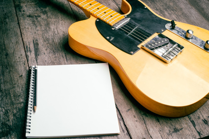 Telecaster electric guitar with notepad on wood desk